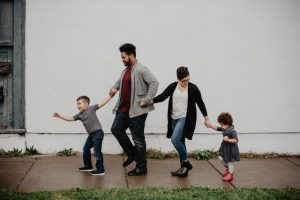 Family Of Four Walking At The Street